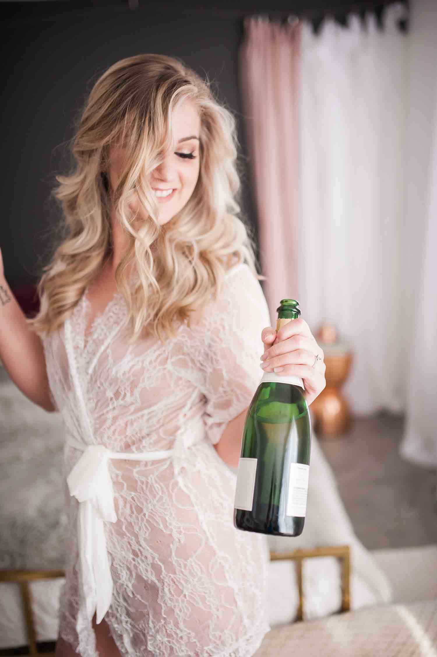 Gorgeous Woman Popping a Bottle of Champaign in an Elegant Silk Robe During Stephanie Marie Photography Iowa City Boudoir Session